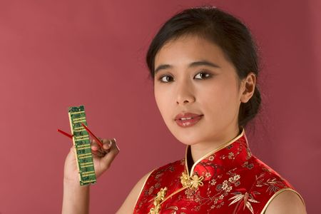 Portrait of young beautiful Chinese female in traditional clothes (cheongsam) holding computer memory chip by chopsticks photo