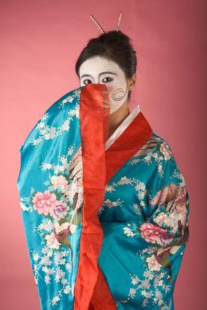 Asian female with geisha style face paint in yukata (kimono) photo