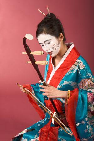 Asian female with geisha style face paint in yukata (kimono) playing erhu