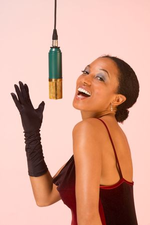 dark skinned y female sings by microphone Stock Photo