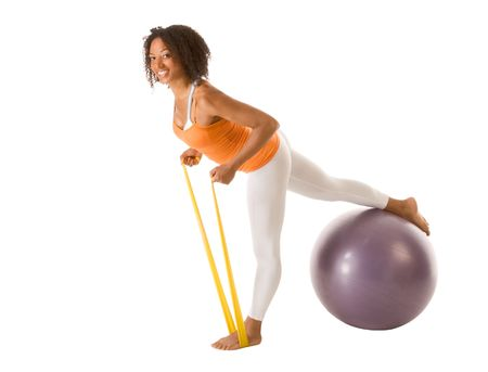 Tanned female performing stretching exercises using resistance bands and sport ball  photo