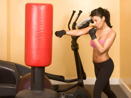 Attractive woman kickboxing with red punching bag Stock Photo