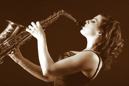 Woman with saxophone in retro lingerie. Image stylized as old picture including adding some artificial grain. Filtered version of picture # photo