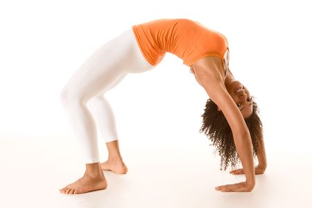 Dark skinned fit woman holding bridge stretching pose