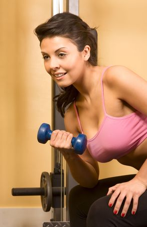 athleticism: Young female working out with small dumbbell in fitness club Stock Photo