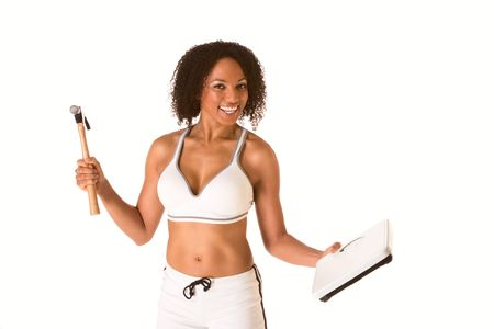 southern european descent: Ethnic woman in sporty outfit hits weight scales by hammer Stock Photo