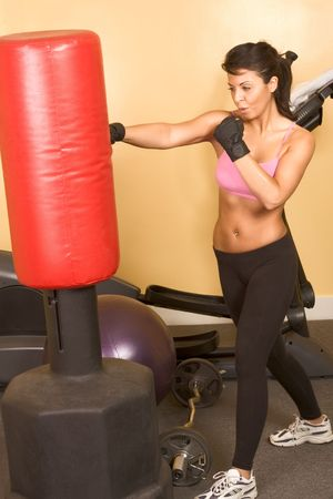 Attractive young woman training kickboxing using red punching bag photo
