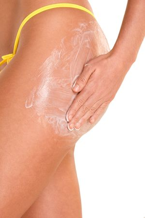 female putting moisturizer on her hips (close up) photo
