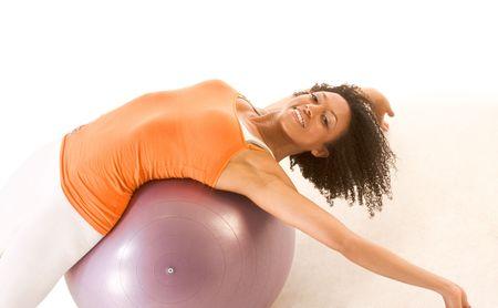 brunete: Dark skinned female stretching on exercise ball  Stock Photo