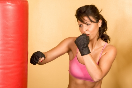 Attractive female kickboxing with red punching bag