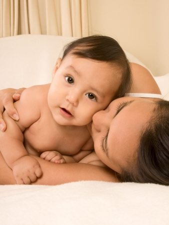 Mom and son lying down on bed and mother embracing the infant baby, who looks at camera with serious facial expression photo