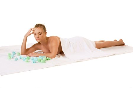 Attractive young female relaxing in spa surrounded by aromatherapy items photo
