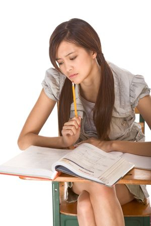 exams: Asian student girl sitting by the desk and studying huge math book, preparing to test