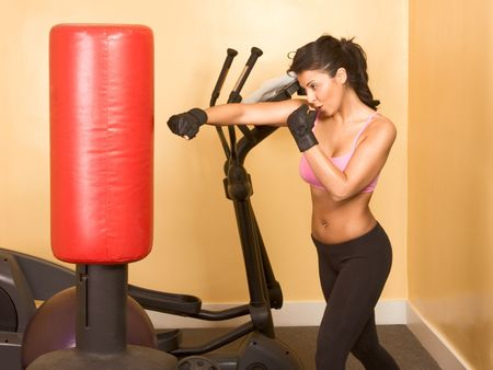 Attractive woman kickboxing using red punching bag Stock Photo
