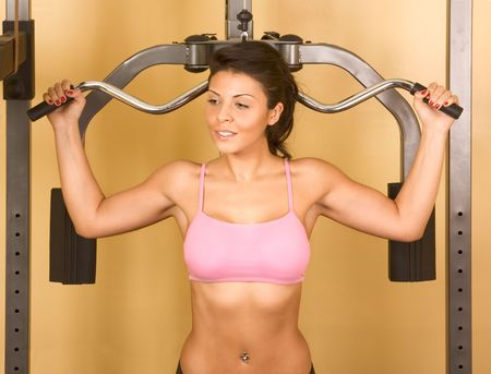 Young woman works out on weight-training machine photo