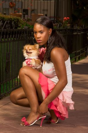 Attractive Afro-American young woman squatting and holding small dog of Pomeranian Spitz breed on her laps, glamour, glamorous photo