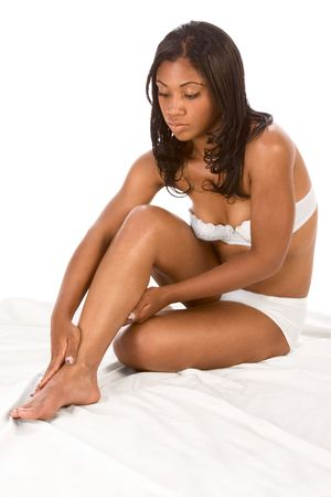 African-American young woman in white lingerie sitting on bed sheet and massaging her legs. photo