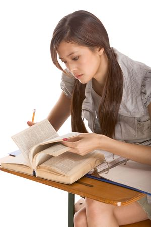 Asian student girl sitting by the desk and studying English dictionary in preparation for test, exam or spelling bee contest photo