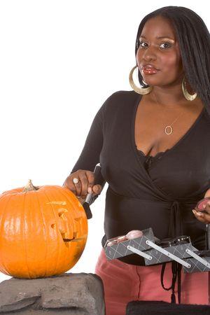 make up artist: Beautiful African-American make up artist applying makeup on Halloween carved pumpkin (Jack O Lantern)