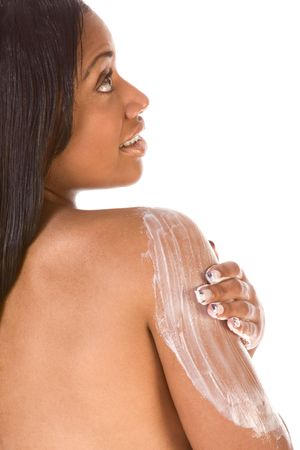 African-American young woman applying cream on her shoulder (back view) Stock Photo - 3388343