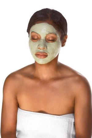 African-American young woman wrapped in towel sitting relaxed with closed eyes and facial mask, undergoing skincare procedure photo