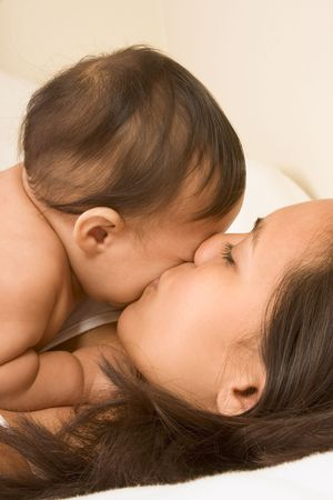 Mom and son lying down on bed and mother kissing the   photo