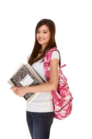 Friendly Asian High school girl student standing in jeans with backpack and holding notebooks and composition book photo