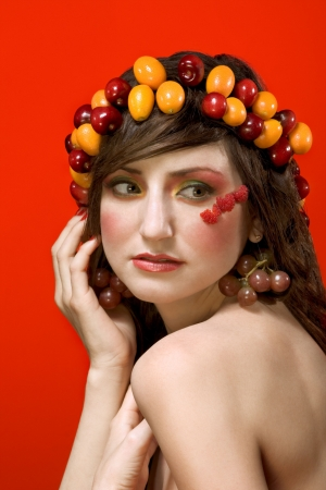 Portrait of young beautiful woman decorated by fruits and berries - diadem of sweet cherries and Miniature Orange (Calamondin, Kalamansi), earrings from grapes and application from red raspberries photo
