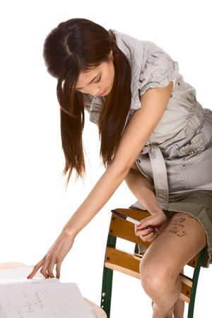 school desk: Young Asian female student cheats during mathematics exam using looking up calculus formula written on her thigh  Stock Photo