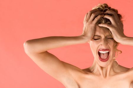 Portrait of gorgeous blonde female holding head and screaming