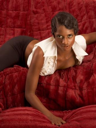 Glamorous retro style (20s) dark skinned sensual female lying down on red sofa Stock Photo - 3476617