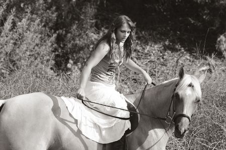 Attractive girl riding on horse in deserted rural location photo