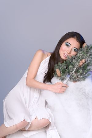 Asian girl by branches of Christmas tree photo