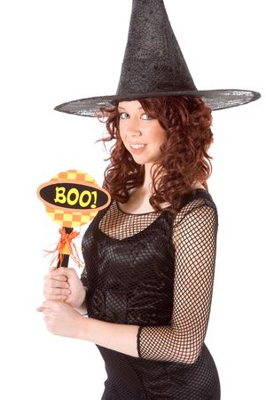 Portrait of Hispanic teenager girl in black Halloween hat and fishnet dress holding boo! sign photo
