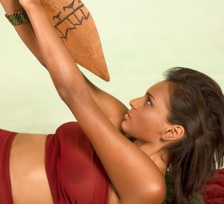 Beautiful ethnic female lies down on back struggling to push away wooden lance that she attacked with
