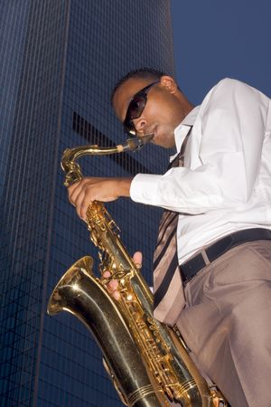 African American man in buttoned white shirt and tie playing on saxophone standing by reflective tall blue office building (low angle view)
