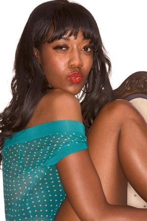 Portrait of sexy Afro-American young woman sitting on chair in sensual pose, knees up Stock Photo - 3544027