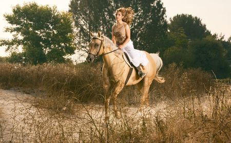 Attractive girl riding on horse in early morning, deserted rural location photo