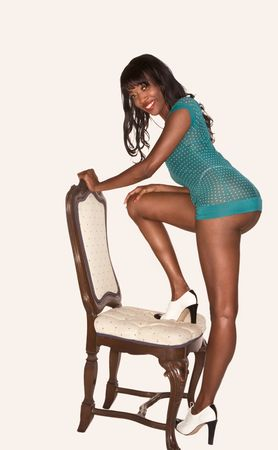 Sensual young black woman with perfectly shaped long legs standing on foot on chair and teasing by demonstrating her rear end