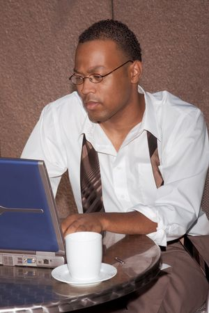 Businessman working notebook laptop computer sitting by the coffee table of some cafe outdoors