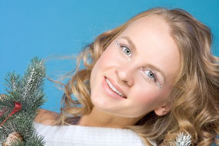 Portrait of mid-aged beautiful blonde female surrounded by branches of decorated Christmas tree photo