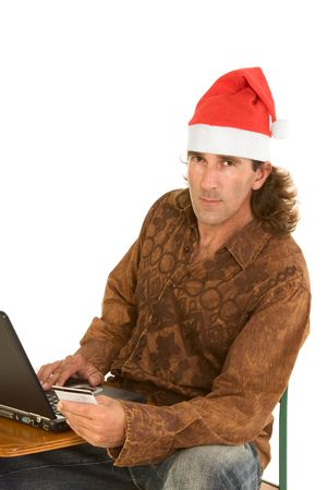 Friendly Middle aged male in Santa hat shopping on-line sitting with portable notebook computer and holding credit card in his hand photo