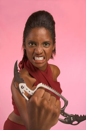 Dark skinned female with wild fanatical facial expression stretch out hand with Brass Knuckle Push Knife Stock Photo