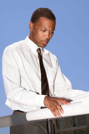 アフロアメリカン: 白いシャツとネクタイで魅力的なアフリカのアメリカの建築家のペーパーワークと青写真を調べます