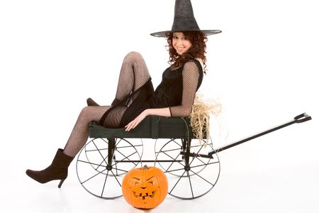 Portrait of Latina teenager girl in black Halloween costume (fishnet dress) sitting on farm cart in straw with carved pumpkin (Jack O Lantern) on the floor Stock Photo
