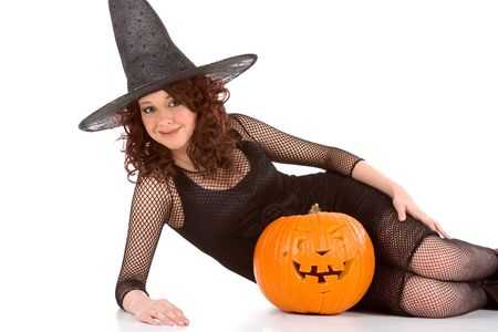 Portrait of Latina teenager girl in black Halloween hat and fishnet dress with carved pumpkin (Jack O Lantern) photo