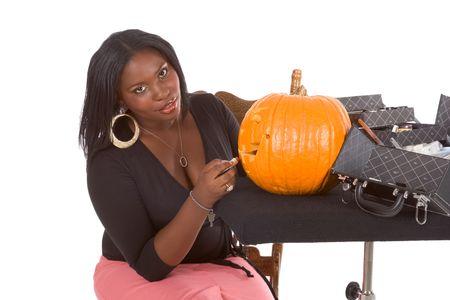 Afro-American female make up artist applying makeup on Halloween carved pumpkin (Jack O Lantern) photo