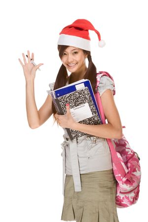 Asian school girl wearing red Santa Claus hat with backpack holding Composition book, notebooks and pen waives her hand making greeting gesture photo