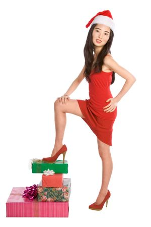 Asian female posing on heap of Christmas gift boxes photo