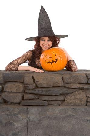 Portrait of Hispanic teenager girl in black Halloween hat and fishnet dress with carved pumpkin (Jack O Lantern) photo